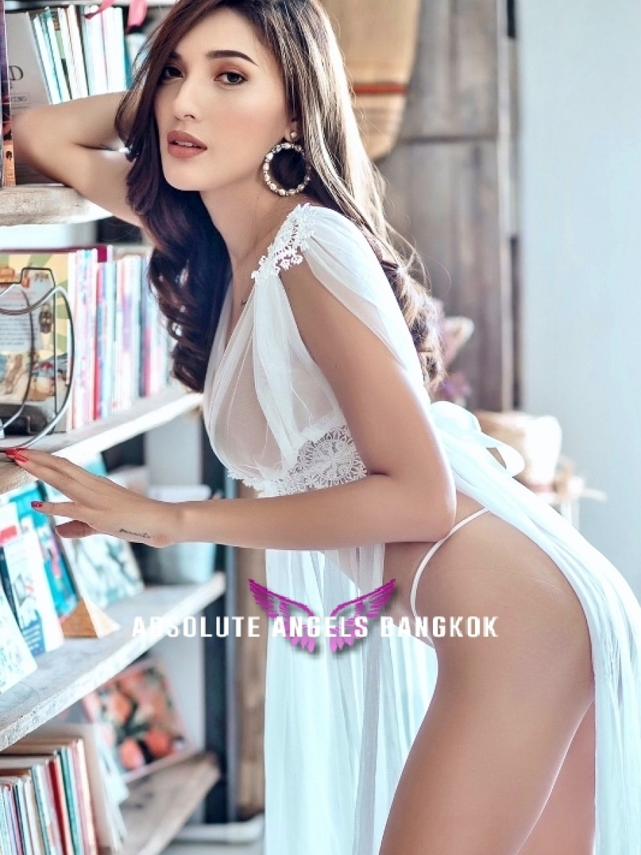 Escort girl Nook with dark hair and tan skin wearing a white shoal leaning on book shelf.
